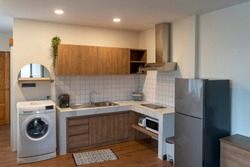 Modern light interior of kitchen with furniture and Various electrical appliances (Washing machine, refrigerator, microwave). White and brown modern kitchen with wooden clear tone in Japanese style.