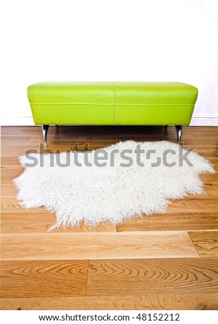 Modern lime green furniture set against a white wall on a polished wooden floor also featuring and angora fleece