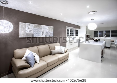 Modern living area with sofa and pillows illuminated by hanging lamps with white walls
