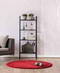 modern living room bookshelf behind stone soft wall with red carpet