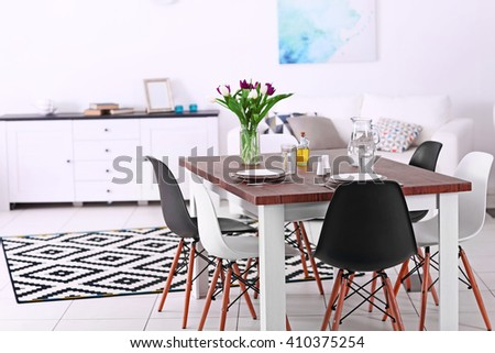 Modern living room. Furniture set with table and chairs. Bouquet of beautiful purple tulips on the table