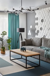 Modern Living Room .Grey sofa and cyan blanket,carpet and curtains.Decorative honeycomb on the wall.Modern floor lamp. Design interior. Grey,white cyan colors.Closeup