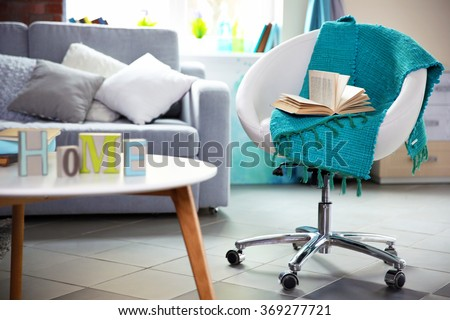 Modern living room interior in grey tones with bright blue plaid and book on chair #369277721