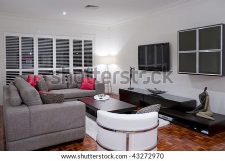 modern living room interior with charcoal sofa and chocolate brown coffee table and wide screen plasma TV. - stock photo