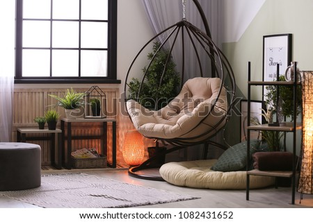 Modern living room interior with floor lamp and hanging armchair