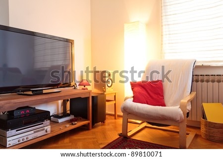 Modern living room - TV and hi-fi and chair - soft ambient light