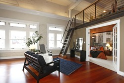 Modern living room with brick painted wall, hardwood floor and iron steep stairs. View of bedroom