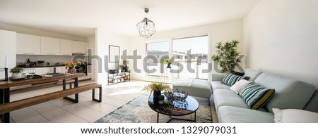 Modern living room with designer sofa and coffee table. Wooden table set with plates and cutlery. Nobody inside