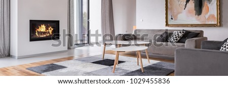 Modern living room with fireplace, sofa, balcony and pattern carpet, panorama