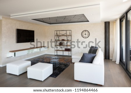 Modern living room with leather sofa and large windows. Nobody inside