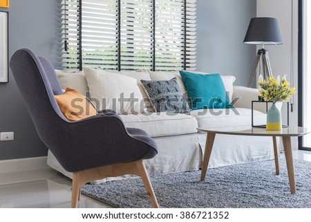 modern living room with modern chair and sofa with vase of plants at home