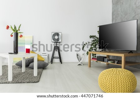 Modern living room with simple but trendy furniture and a tv set, arranged in grey and yellow