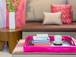 Modern living room with sofa and cup of coffee  in colorful tray