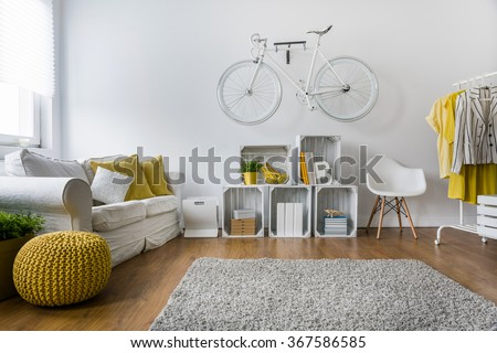 Shutterstock Modern living room with sofa, carpet, wood panels and bike hanging on wall