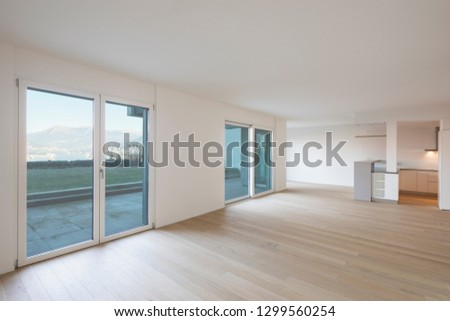 Modern living room with white walls, parquet and windows with mountain views. Nobody inside