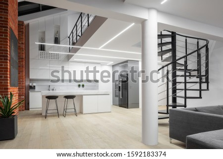 Modern loft apartment with mezzanine floor, brick walls and kitchen open to living room