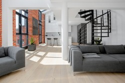 Modern loft apartment with red brick on the walls, big windows, black stairs and kitchen open to living room
