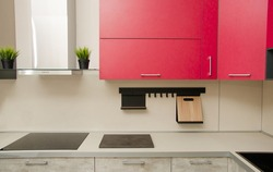 modern loft-style kitchen with red cabinets, stove, range hood and table with countertop.