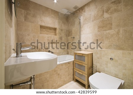 modern luxury bathroom with beige marble stone tiles and white ceramic suite - stock photo