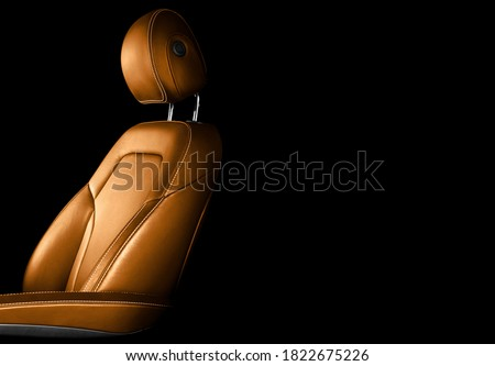 Modern luxury car brown leather interior. Part of orange leather car seat details with white stitching. Interior of prestige car. Comfortable perforated leather seats. Perforated leather.