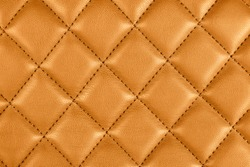 Modern luxury car brown leather interior. Part of perforated leather car seat details. Orange perforated leather texture background. Texture, artificial leather with diagonal stitching.