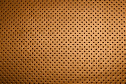 Modern luxury car brown leather interior. Part of perforated orange car seat details. Perforated leather texture background. Texture, artificial leather with stitching. Perforated leather seats