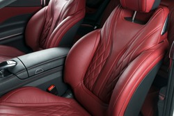 Modern Luxury car inside. Interior of prestige modern car. Comfortable leather red seats. Red perforated leather cockpit with isolated Black background. Modern car interior details