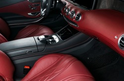 Modern Luxury car inside. Interior of prestige modern car. Comfortable leather seats. Red perforated leather cockpit. Steering wheel and dashboard. automatic gear stick shift. Car interior details