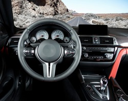 Modern luxury car Interior - steering wheel, shift lever and dashboard. Car interior luxury.Steering wheel, dashboard, speedometer, display. Red and black perforated leather cockpit. Car on the road