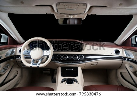 Modern luxury car Interior - steering wheel, shift lever and dashboard. Car interior luxury. Beige comfortable seats, steering wheel, dashboard, speedometer, display. Red and white perforated leather. #795830476