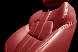 Modern luxury car red leather interior. Part of red perforated leather car seat details with white stitching. Interior of prestige car. Comfortable perforated leather seats. Perforated leather.