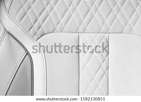 Modern luxury Car white leather interior. Part of perforated car seat details. White Perforated leather texture background. Texture, artificial leather with stitching. Perforated leather seats
