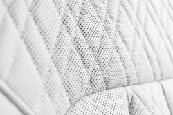 Modern luxury Car white leather interior. Part of perforated leather car seat details. White Perforated leather texture background. Texture, artificial leather with stitching. Perforated seats
