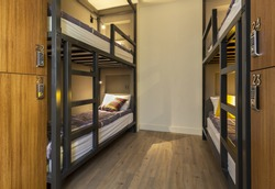 Modern, luxury, hostel, dorm, dormitory, motel room. Wooden floor room full of comfortable beds. Accomodation for students. Bedroom view from a hostel.