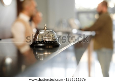 Modern luxury Hotel Reception Counter desk with Bell. Service Bell locating at reception. Silver Call Bell on table, Receptionists and customer on background. Сheck in hotel. Concept.