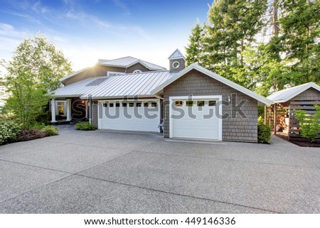 Modern luxury house exterior with curb appeal. View of garage with  driveway and small porch with white columns #449146336