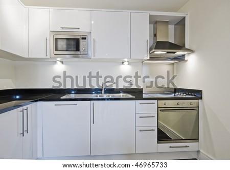 modern luxury kitchen in white with black granite worktop stock photo