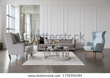 Modern luxury stylish apartment interior in pastel colors. a very bright room with huge windows filled with daylight. white walls, wooden parquet floors and a dark marble fireplace