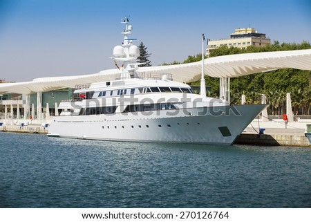 Modern luxury white yacht docked at port during day. stock photo