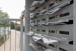 Modern mailboxes filled of flyers. Business and advertising concepts. Shallow depth of field.