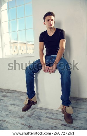 Modern male model posing on light background next to the large windows. Man are in the room near the window light. Handsome man in free space. The concept for the design and advertising.