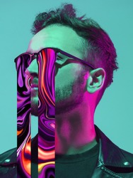 Modern man's portrait in sunglasses isolated on studio background in neon light. Concept of human emotions, facial expression, sales, ad. Stylish creative design, art vision, new look of artwork.