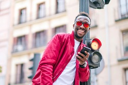 Modern man with sunglasses over a traffic light using mobile phone
