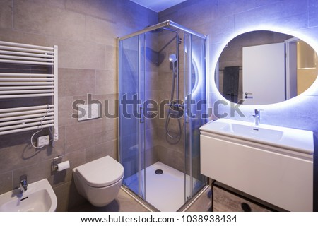 Modern marble bathroom with backlit mirror. Relaxing light. Nobody inside #1038938434