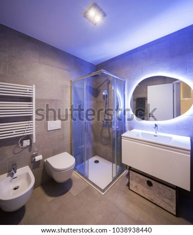 Modern marble bathroom with backlit mirror. Relaxing light. Nobody inside #1038938440