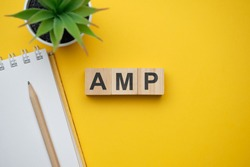 Modern marketing buzzword AMP - Accelerated Mobile Pages. Top view on wooden table with blocks. Top view. Close up.