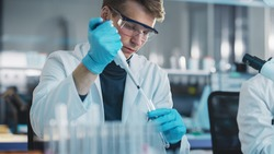 Modern Medical Laboratory: Young Caucasian Male Research Scientist Using Micro Pipette to Mix Chemical Liquids in a Test Tube. Microbiologists Conducting Biotechnology Research. Portrait Shot
