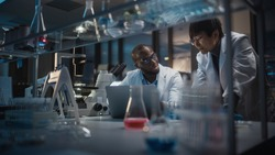 Modern Medical Research Laboratory: East Asian and Black Scientists Work on Laptop, Do Data Analysis, Talk. Advanced Scientific Pharmaceutical Lab for Medicine, Biotechnology Development. Evening Time