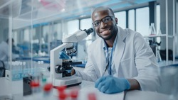 Modern Medical Research Laboratory: Portrait of Male Scientist Using Microscope, Charmingly Smiling on Camera. Advanced Scientific Lab for Medicine, Biotechnology, Microbiology Development
