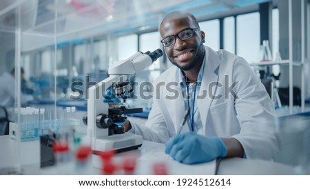 Modern Medical Research Laboratory: Portrait of Male Scientist Using Microscope, Charmingly Smiling on Camera. Advanced Scientific Lab for Medicine, Biotechnology, Microbiology Development Foto stock ©